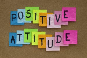 positive attitude concept - colorful sticky notes reminder on cork bulletin board